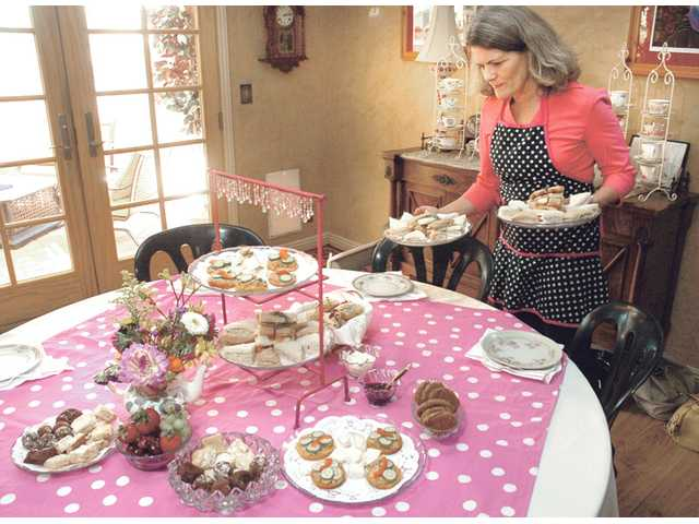 Merry Graham, of Newhall, prepares the bridal tea table for Valencia bride Jenni Blount.