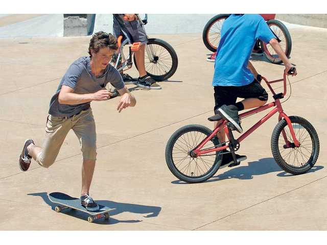 Skateboarder Connor Ford, 17, of Santa Clarita, left, passes a group of BMX riders as they share the use of the Santa Clarita Skate Park on Friday. Both bike riders and skateboarders say they frequently collide while using the park's facilities, but the city said there were few injuries reported there.