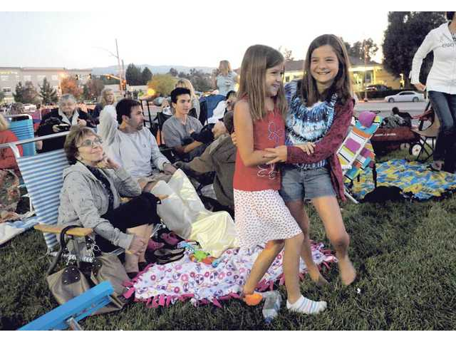 Maddy Anderson, 8, and Ashley Oillataguerre, 9, of Saugus, enjoy fireworks at the Westfield Valencia Town Center on Sunday.