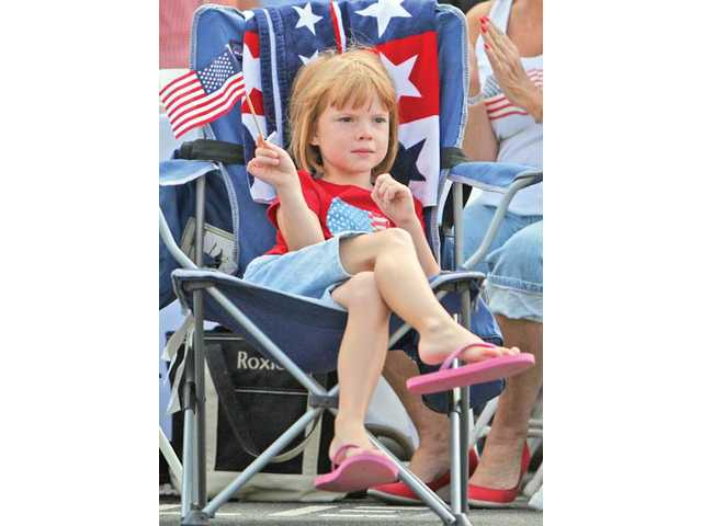 Newhall resident Claire Mortensen, 5, comfortably watches the Santa Clarita Valley Fourth of July Parade go down Main Street on Sunday morning.