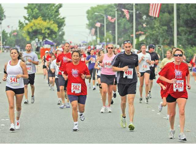 Participants of the Independence Day Classic 5K Run keep pace on Lyons Avenue on Sunday before the Santa Clarita Valley Fourth of July Parade. More than 650 adults and 70 children participated in this year's event.