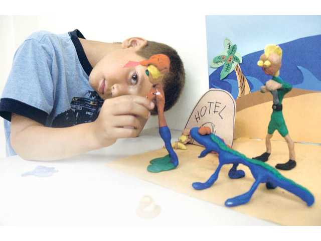 "Owen Kennedy, 7, moves a clay figure a fraction of an inch as he and his team work on a clay-figurine film called ""The So-called Stolen Tooth Brush,"" at an MBK Studios class held in the Santa Clarita Sports Complex in Santa Clarita on Thursday."