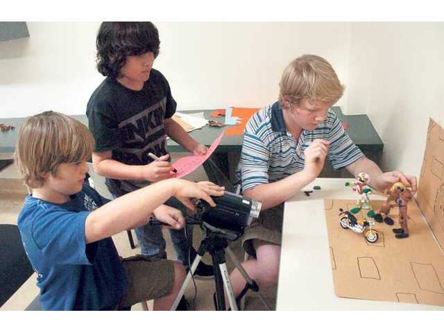 "From left, MBK Studios video-production students, Bailey Marshall, 11, Marc Martinez, 10, and Sage Marshall, 13, film three clay figurines for a film titled, ""The Mummy's Curse"" at the Santa Clarita Sports Complex on Thursday."