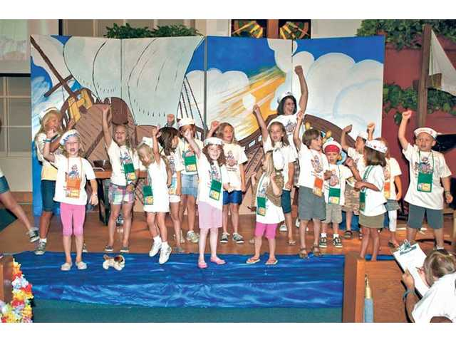 A group of kids belts out a rollicking song of faith while surrounding their music instructor, Marie Gilbert, center. For five days in late June, Gilbert taught the youngsters songs and hand movements at the First Presbyterian Church of Newhall's Vacation Bible School.