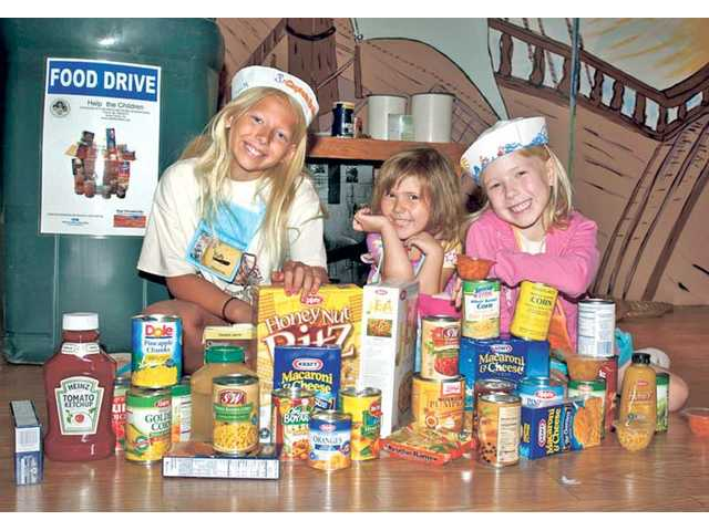 From left, Katie Meyer, Alissa Hartman and Genevieve Wheeler sit with just a few food items collected during First Presbyterian Church of Newhall's Vacation Bible School. Over 450 food items were brought to the church during the week. The collected items were donated to Help the Children — Santa Clarita, a local group providing help to families in the Santa Clarita Valley, which recently moved to a new location at 25030 Avenue Tibbitts, Suite L in Valencia.