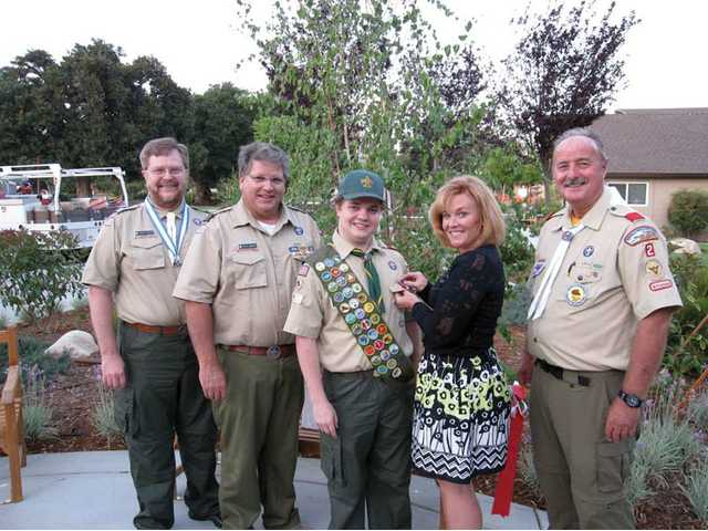 Kevin R. Rodgers, center, receives his Eagle Scout pin from his mother, Beth Rodgers, and his father and scoutmaster, Steve Rodgers, second from left.  Assistant scoutmasters and Eagle Scouts Henry Mowry, far right, and Jim Beydler, far left, participated in the ceremony.