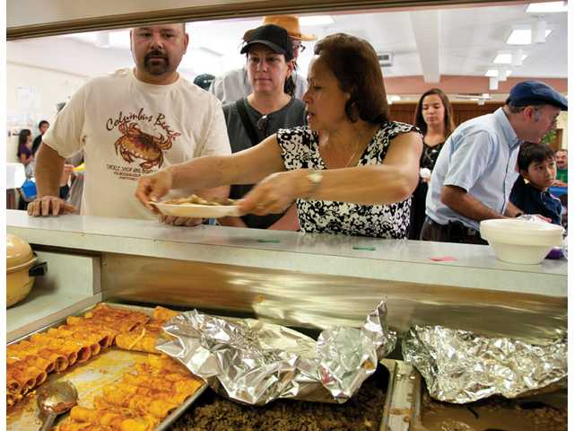 Our Lady of Perpetual Help Church parishioner Mercedes Cruz, center, serves a traditional Mexican meal  to Jose Perez, left, and his wife, Irma, second from left. More than 35 volunteers arrived at the church's Parish Hall at 7 a.m. to prepare for hundreds of guests who came to Newhall to help the Garnica family, after mother Matilde Garnica died in a fatal crash on the Fourth of July.