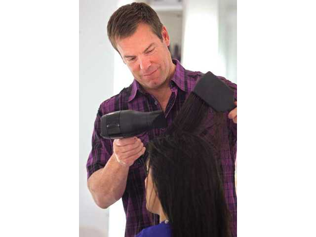 Dave Csicsai, co-owner of Salon glō in Valencia prepares to put L'Oreal's Kérastase Resistance Ciment Thermique, a leave-in heat-activated reconstructor milk before blow drying.