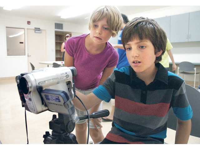 "Olivia Kennedy, 9, and Zane Swift, 10, line up the camera as they work on their video titled ""The So-Called Stolen Toothbrush"" at an MBK Studios video-production class held at the Santa Clarita Sports Complex."