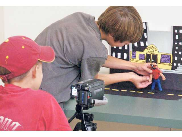 """MBK Studios video production students Ian Andersen, left, fires the camera one frame at a time as Nick McIlrath moves their claymation character as they film their video entitled """"Revenge of the Cyborg Nerd."""""""
