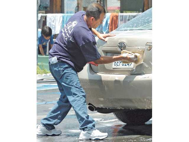 Juan Orona joins volunteers who washed an estimated 100 cars by 1 p.m. to benefit the Garnica family at the daylong car-wash fundraiser at the Mulberry Mobile Home Park in Newhall on Saturday.