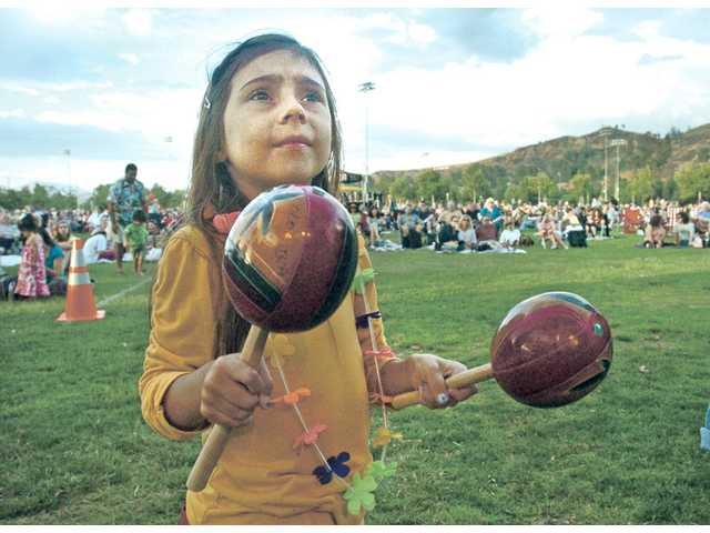 Morgan Duryea, 5, shakes a pair of maracas as she plays along with the Latin guitar band Incendio at the kick off of the Concert in the Parks on Saturday.