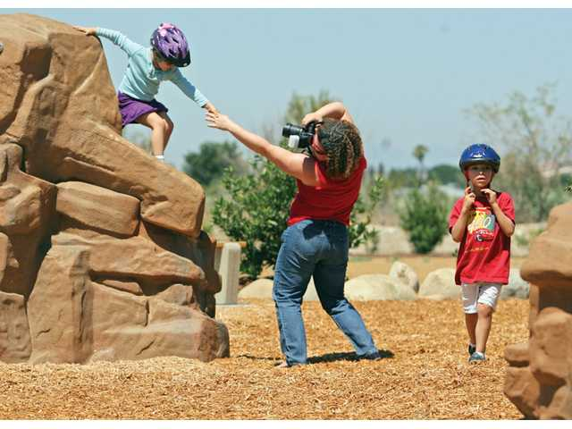 Gabriela Cardenas, center, photographs daughter, Iuliana, 5, as her son Daniel Cardenas walks by at Discovery Park in Canyon Country.