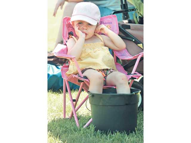 Miranda Fox, 2, of Valencia, sits with her feet in a bucket of water to keep cool as she waits for her brother's soccer game to start at the Santa Clarita Valley Magic Cup tournament at Old Orchard Park on Saturday.