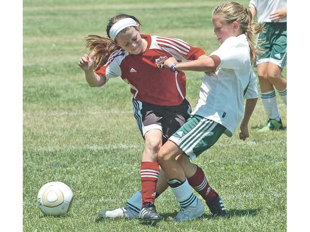 Santa Clarita Magic team member Alyssa Williams, right, fights for the ball against her opponent Maria Cabrera in the SCV Magic's 6-0 victory over the San Luis Obispo Storm, in the girls-under-10 category at the Magic Cup.