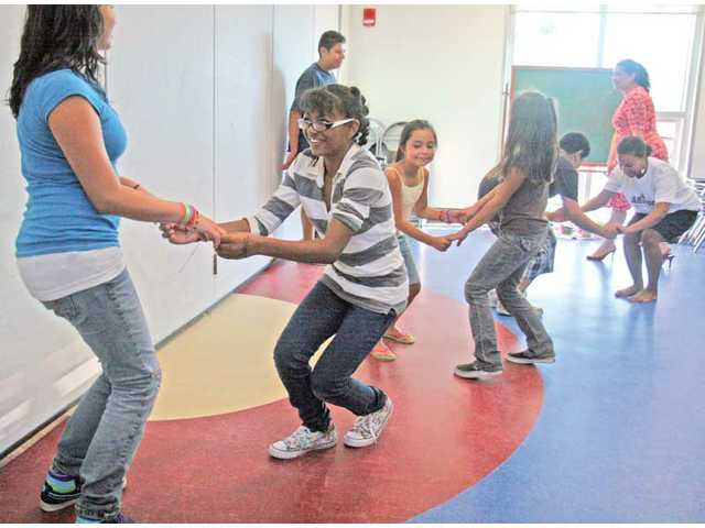 A group of kids dance merengue and salsa during a class.