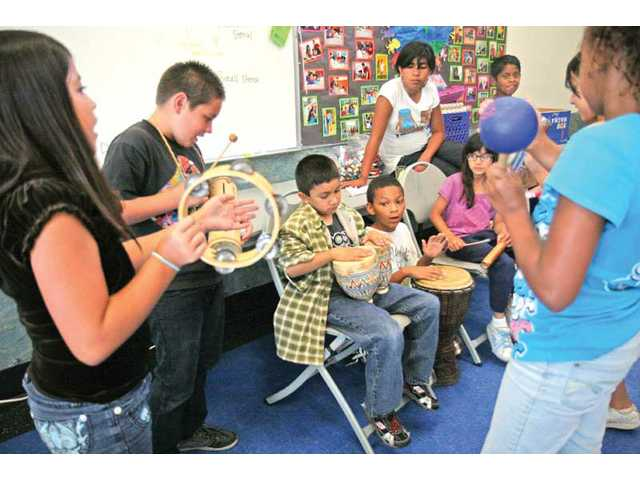 Young children play various instruments used in a salsa ensemble to create their own beats during performance and visual classes for kids at the Newhall Community Center on June 30. The exhibit was put on by the ARTree, an organization that would like to have the Community Center offering classes, exhibits, performances and art education for children and their parents.