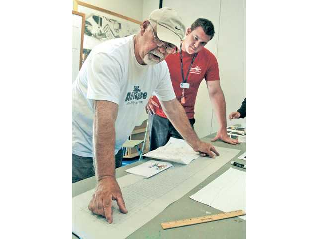 Bob Hernandez, left, of The ARTree and Team Project Coordinator Justin Hillemann look at a sketch of a Newhall warehouse that will be covered with a 100-foot mural designed and painted by the Newhall Community Center team.
