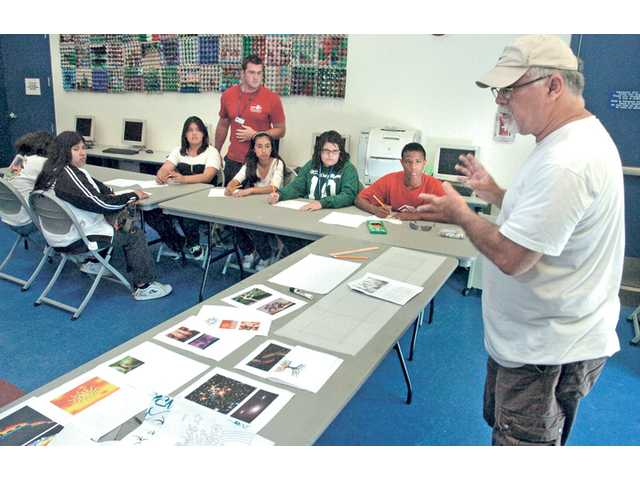 Bob Hernandez, right, of The ARTree discusses the design elements suggested by a team of teens at the Newhall Community Center for a 100-foot mural that will be painted on the side of a Newhall warehouse.