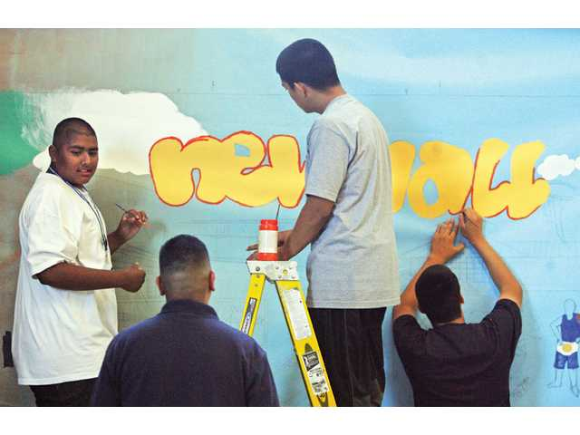 Jose Meza, 17; Sports Coordinator Efren Galindo; Taylor Corona, 16; and Arturo Sanchez, 15, start the painting process of the mural.