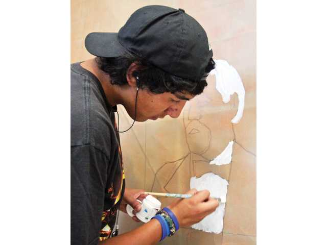 George Lara, 16, of Canyon Country, works on the portrait of Henry Mayo Newhall at the SCV Community Center on June 13, which will be part of the five-panel mural developed and created by local teens through The ARTree program.
