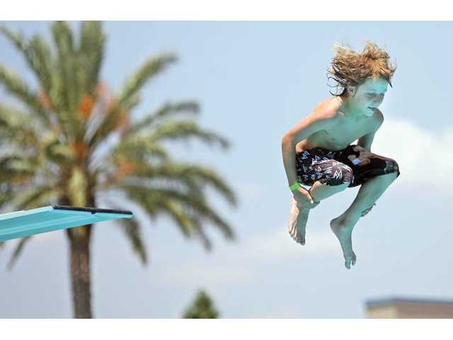 Eleven-year-old Tieler Janeck, of Valencia, jumps off the diving board at the Santa Clarita Aquatic Center on Thursday.