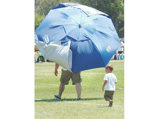 Grant Holladay, 3, of Bakersfield, follows his dad, Brandon, as he carries an umbrella across the soccer field before the start of a Santa Clarita Valley Magic Cup soccer-tournament match held at Hart High on Saturday.