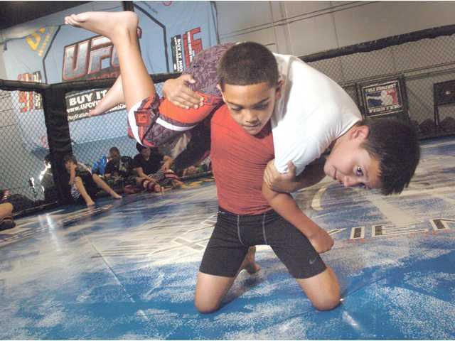 Isaac Salas, 8, lifts James Gonzalez, 9, in a fireman's carry takedown as they train at Big John McCarthy's Ultimate Training Academy in Valencia on Thursday.