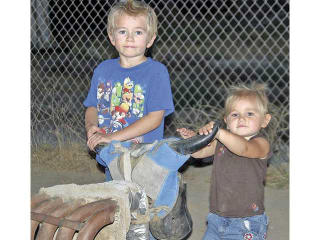 Scott Swetnam Jr., 4, and his sister Shelby, 1-1/2, try out their roping skills with a pair of cow horns at the Cops and Cowboys event. The event benefited the Mid-Valley Community Police Council. More than $20,000 was raised. The event attracted more than 300 attendees. The event was held in the SCV to be accessible to where LAPD officers live.