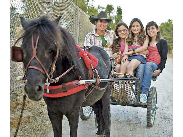 Mini Cooper, a miniature horse, and Kristin Tesiny give a cart ride to Guilianna Meltzer, Lauren Feder and Sarah Greenlee at the 2010 Cops and Cowboys event held at the VFW Post on Sierra Highway in Canyon Country.