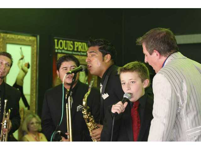 "Twelve-year-old Anthony Prima sings a bit of ""Just a Gigolo"" with his father, Louis Prima Jr. (right), with a little help from Witnesses bandmembers (from left) Ted Schumacher, Phil Clevinger and Marco Palos after dedication of Louis Prima Sr.'s star on the Hollywood Walk of Fame Sunday."