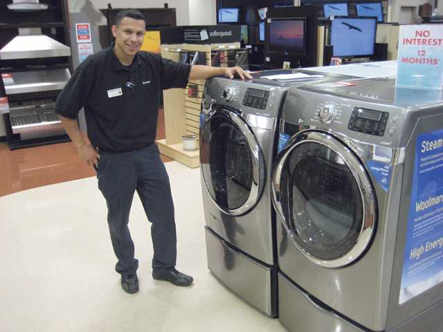 Emanuel Martinez, store manager at Pacific Sales in Valencia, stands next to a top-of-the-line washer/dryer pair from Samsung.