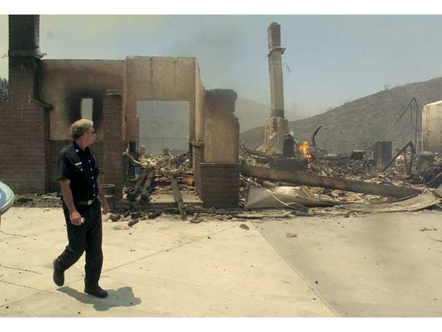 Fire Captain Jerry Meehan surveys the Crown Fire's damage to a single-family home in Leona Valley on Friday.