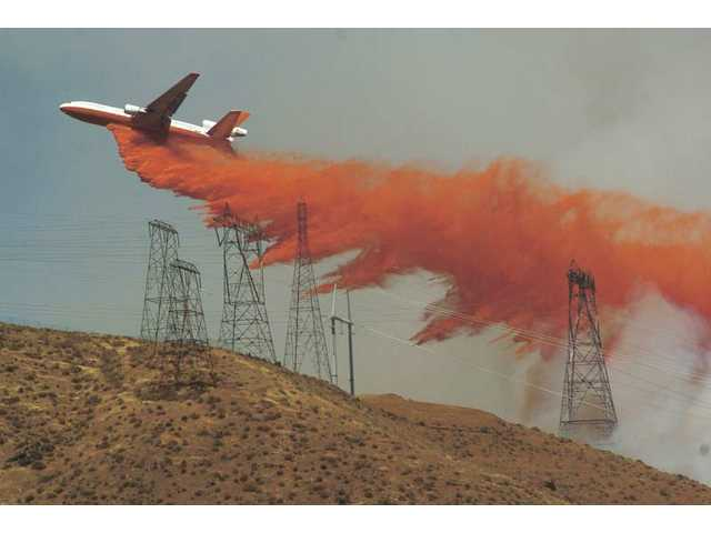 A DC-10 fire tanker drops fire retardant near power lines by Godde Hill and Lake Elizabeth roads in Leona Valley on Friday.