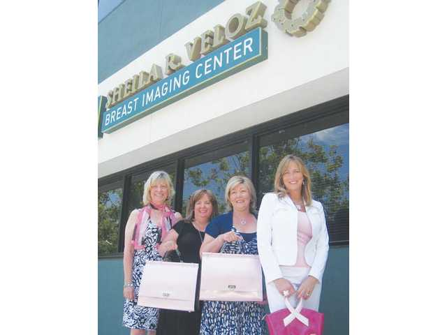 "Donna Kreutz, member of Soroptimist International of SCV and breast cancer survivor, left, along with fellow Soroptimists and Susan Handley, owner and designer of Beijo Bags, right, presented pink Beijo ""comfort bags"" filled with goodies to breast cancer survivors, Robin Castagnola and Cherie Balousek, center, at the Sheila R. Veloz Breast Imaging Center in Valencia."