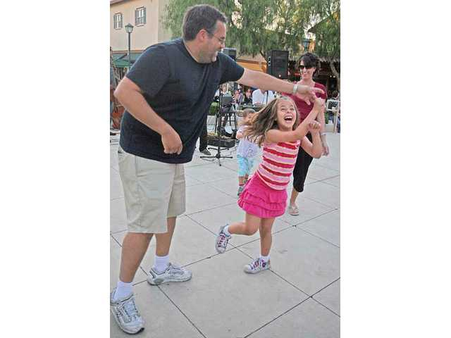 Jed Blaugrund twirls his 7-year-old daughter, Riley, as his wife, Daryl, dances with their 4-year-old son, Bryce, in the background during Friday's Summer Sunset Concert Series on Friday at Valencia Marketplace in Stevenson Ranch.
