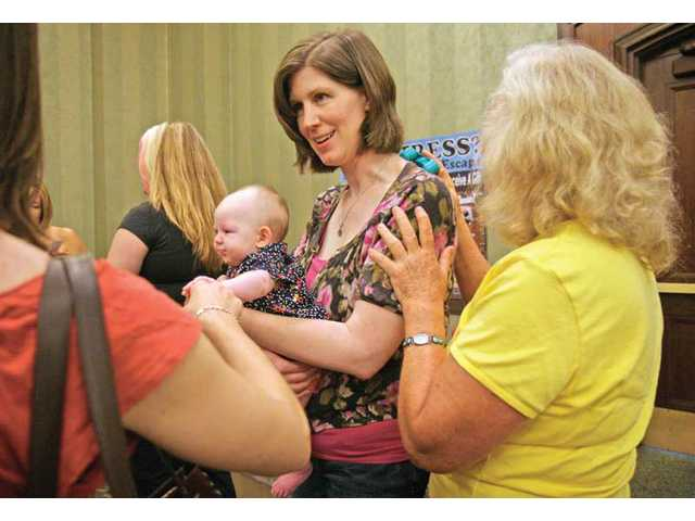 Saugus resident Cassandra Firemark, holding 3-month-old Lily Firemark, gets a massage from Marianne Prottung, right, during The New You Womens Expo at the Hyatt Regency Valencia on Saturday.