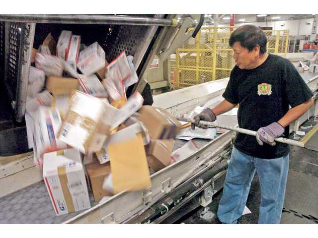 Castaic resident and 25-year postal employee Jimmy Barlan moves parcels on to a conveyor as he works the late shift at the Santa Clarita Processing and Distribution Center in Santa Clarita on Thursday.