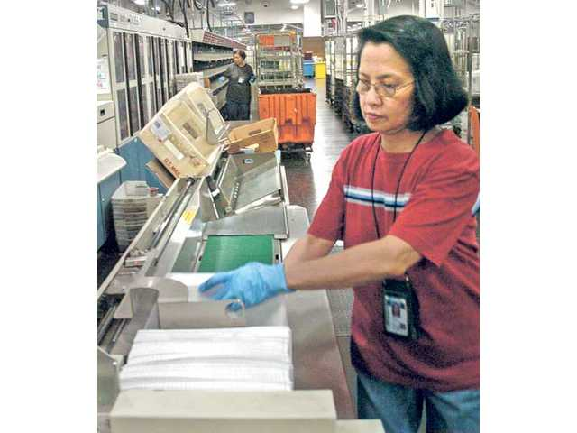 Nely Inoce Ida, right, and Linda Manansala, both 27-year postal employees, sort mail at the Santa Clarita Processing and Distribution Center during the night shift Thursday.