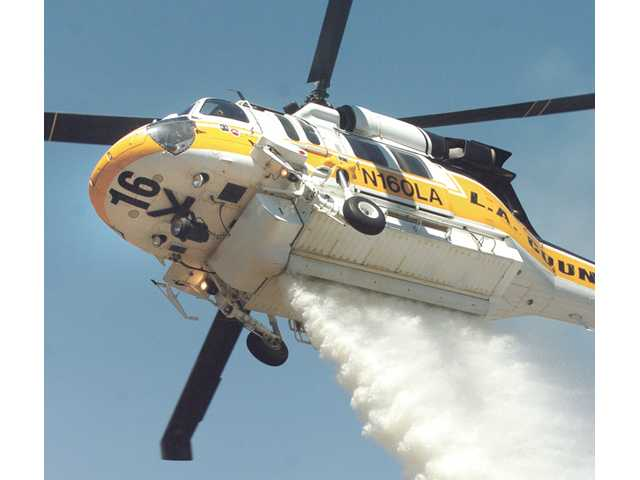 A Los Angeles County helicopter drops water on flames that climbed a steep hill toward homes in the Leona Valley on July 31.