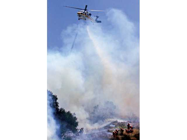 "A Los Angeles County Fire Department helicopter makes a drop over fire crew members at the ""Patrol Incident"" on the northbound side of Interstate 5 south of Calgrove Boulevard on Wednesday afternoon."