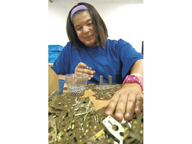 Christina Sears, 20, assembles padlocks at Pacific Locks' warehouse in Valencia. Pacific Locks co-owner Greg Waugh said being part of an enterprise zone rewards his hiring of additional workers.