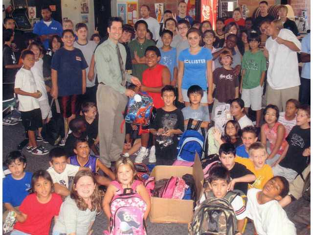 Dr. Roger De Sesa stands amongst the kids at the Boys & Girls Club of Santa Clarita Valley after dropping off backpacks donated by his customers for the kids in 2009.