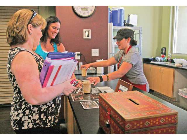 Debie Kimball, left, and Marilyn Lombardi get iced-coffee drinks from Undergrounds coffee shop volunteer manager Kelly Boek on Tuesday afternoon.