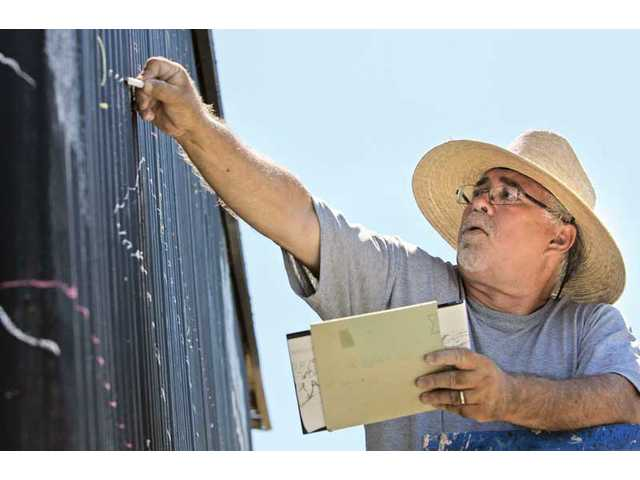 In a recent photo, ARTree President Bob Hernandez helps work on a mural on a building next to the organization's future home, the ARTree Community Arts Center, in Newhall.