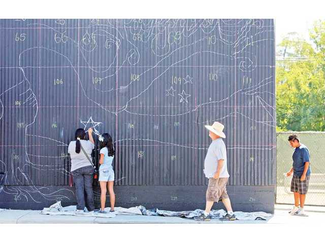 Local youths and artists trace chalk on a wall for a mural. The ARTree is a nonprofit organization that introduces arts to children.