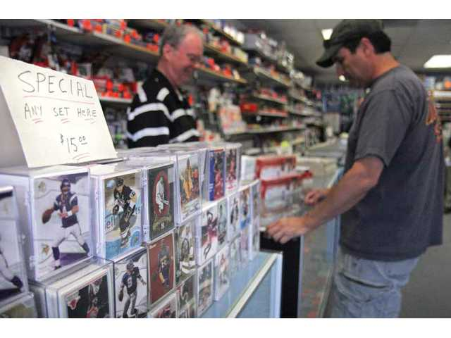 Card Connection owner Mike Manning, left, helps a customer Wednesday at his shop in Newhall. Card Connection has been at its current location for 18 years.