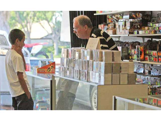 Eleven-year-old Jeremy Espinosa, of Newhall, asks Card Connection owner Mike Manning about a gaming card Wednesday.