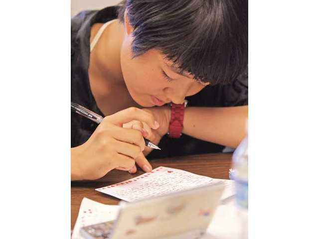 Dolly Ye, 13, writes a letter to her local sponsor family at Grace Baptist Church on Monday. A total of 30 Chinese students ranging in age from 12 to 16 traveled to America and studied for three weeks in the EF Language Travel program. The students went home Tuesday.