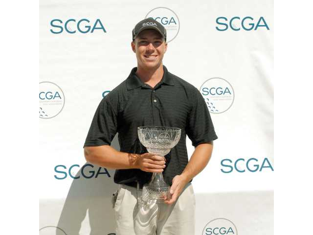 Saugus High graduate Nick Delio holds the Southern California Golf Association Match Play Championship trophy on Wednesday at Sandpiper Golf Club in Santa Barbara.
